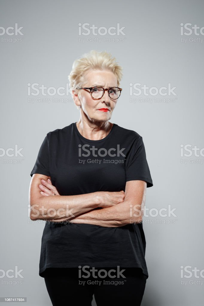 Portrait of powerful senior woman Displeased senior woman wearing black clothes, standing with arms crossed against grey background, staring at camera. Studio shot. Active Seniors Stock Photo