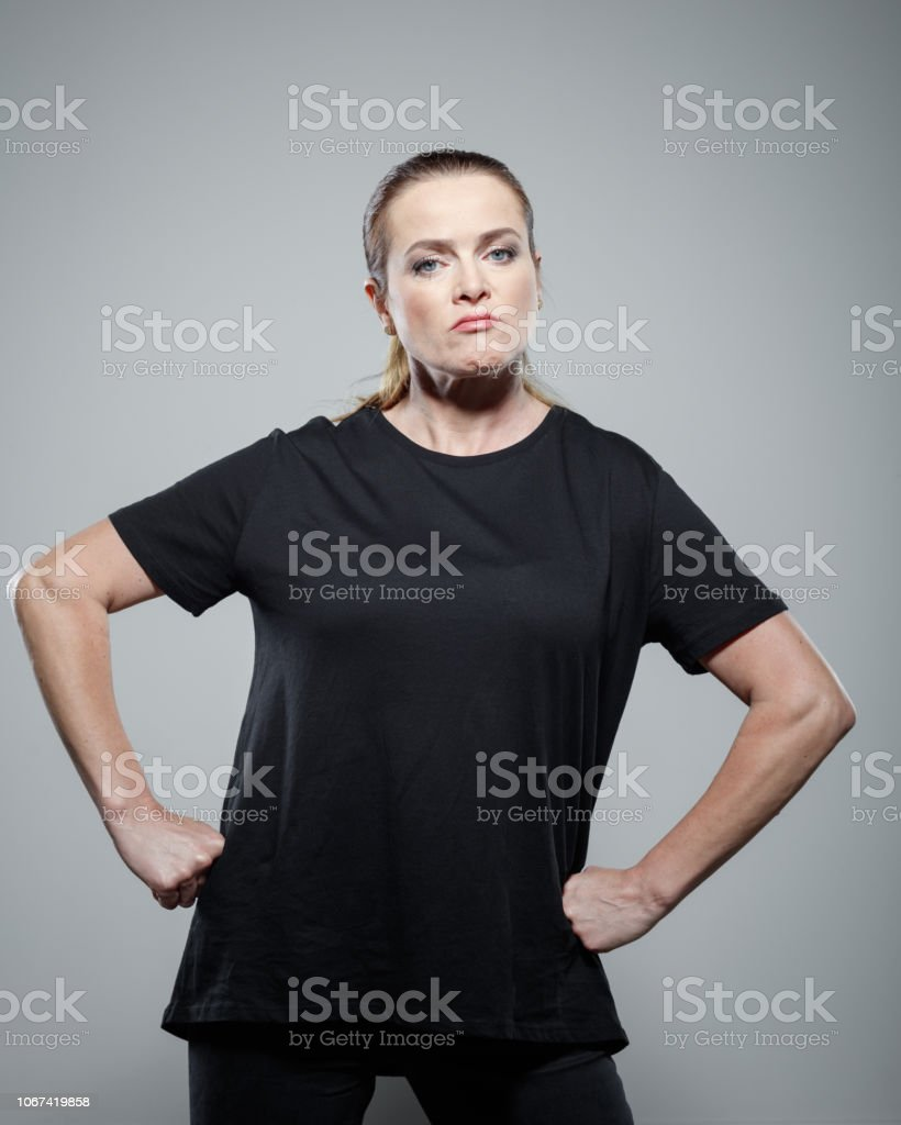 Portrait of powerful woman Strong woman wearing black clothes, standing against grey background, staring at camera, clenching fists. Studio shot. 35-39 Years Stock Photo