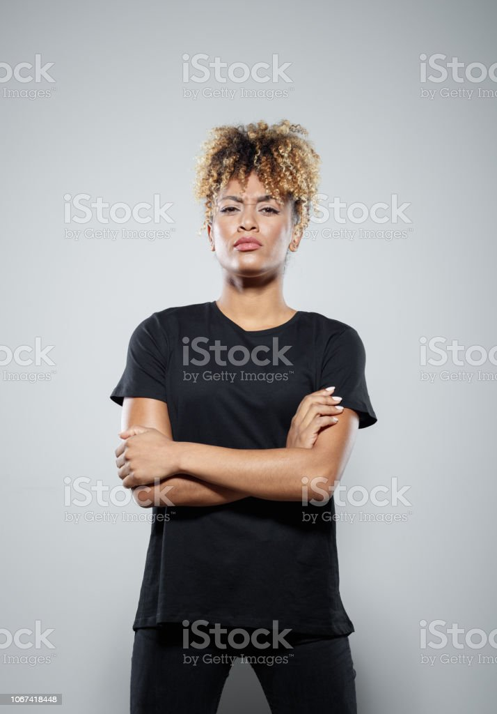 Portrait of powerful young woman Strong young woman wearing black clothes, standing with arms crossed against grey background, staring at camera. Studio shot. Activist Stock Photo