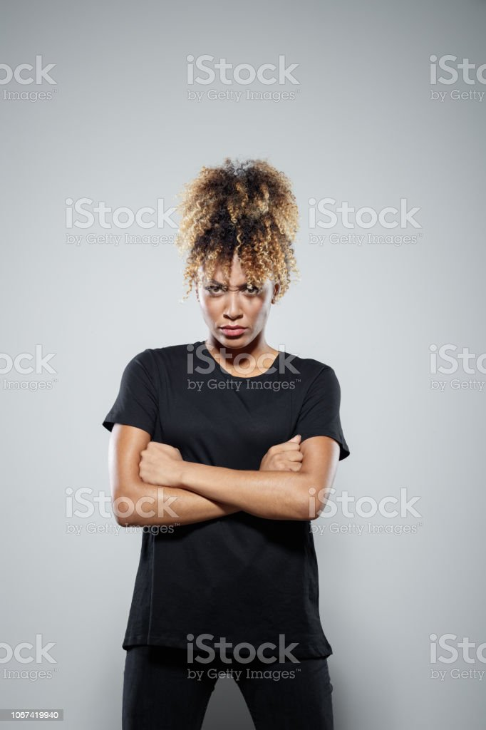 Portrait of powerul angry young woman Strong young woman wearing black clothes, standing with arms crossed against grey background, staring at camera, clenching fists. Studio shot. Activist Stock Photo