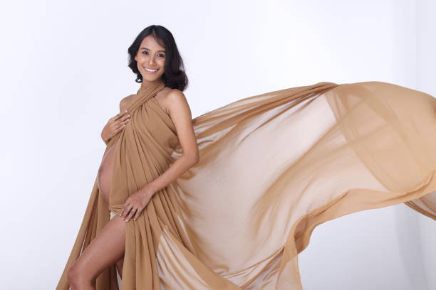 Portrait of Pregnant Asian Indian tanned skin woman fabric fluttering in Air - foto stock