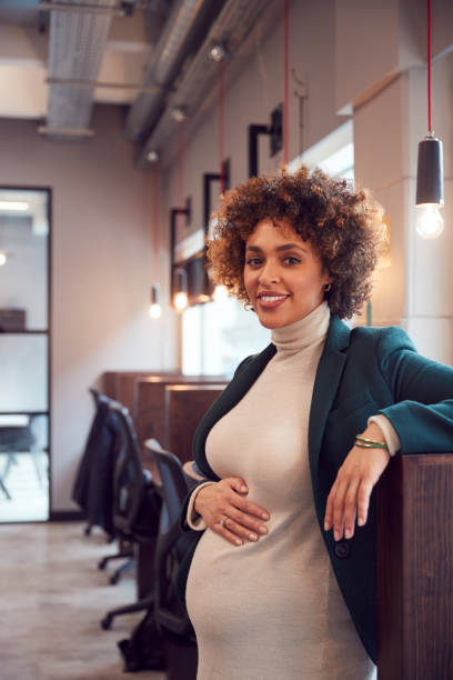 Portrait Of Pregnant Businesswoman Holding Bump Working In Modern Office stock photo