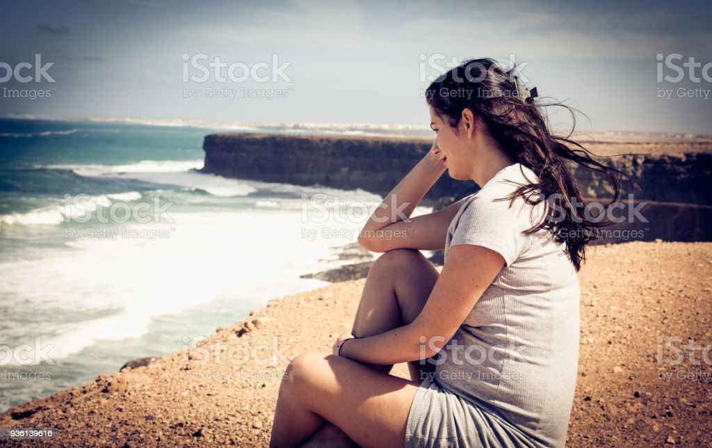 Portrait of pregnant woman sitting at the beach coast. stock photo