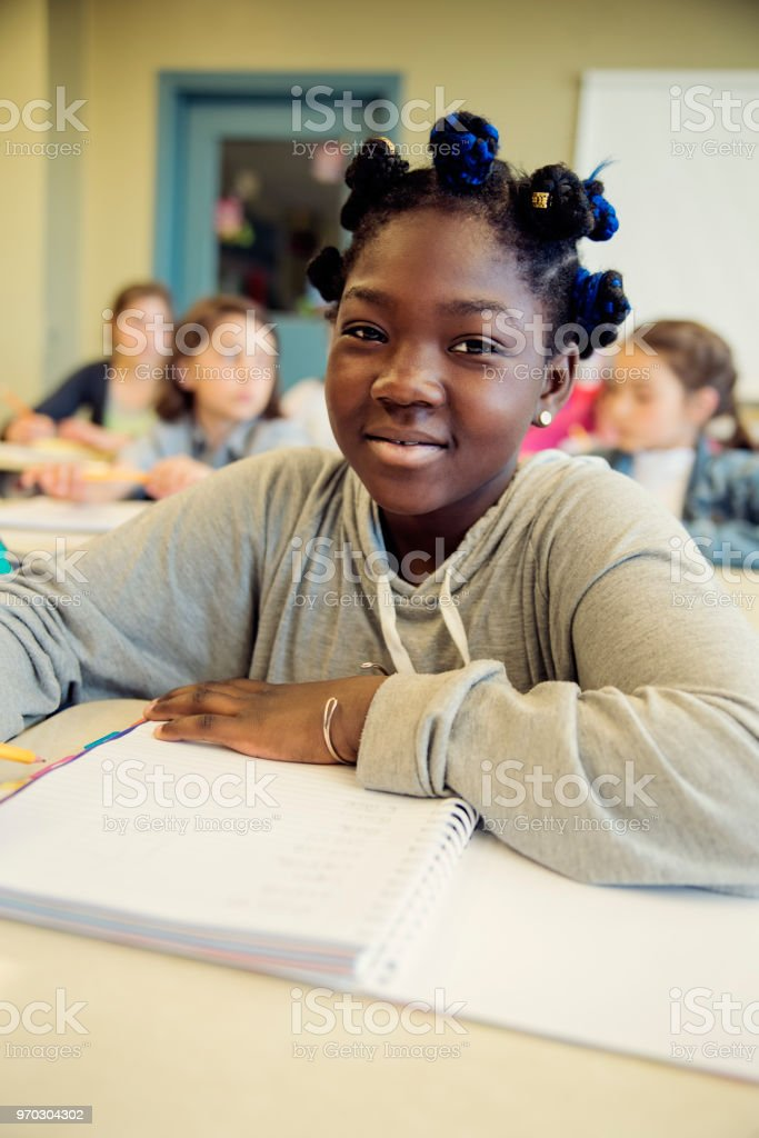 Portrait of preteen African-American girl in classroom, sitting at her desk. royalty-free stock photo