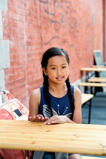 Portrait of preteen girl sitting at a city terrace. stock photo