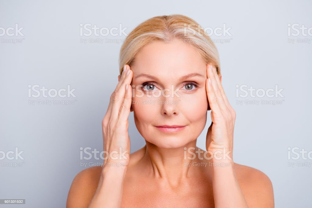 Portrait of pretty, attractive, charming, naked, nude woman touching temples with hands, isolated on grey background,  after peeling, lotion, mask, perfection, wellness, wellbeing, hydration concept foto stock royalty-free