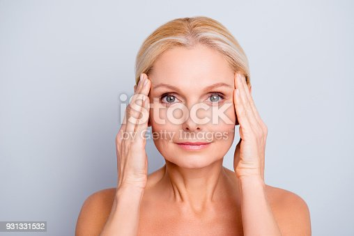 istock Portrait of pretty, attractive, charming, naked, nude woman touching temples with hands, isolated on grey background,  after peeling, lotion, mask, perfection, wellness, wellbeing, hydration concept 931331532