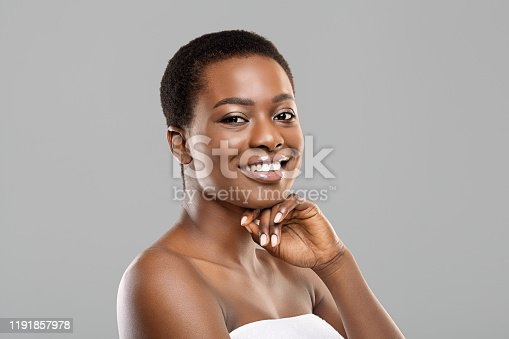 African beauty. Portrait of pretty black woman wrapped in towel after bath, touching her chin and smiling at camera over gray background with copy space