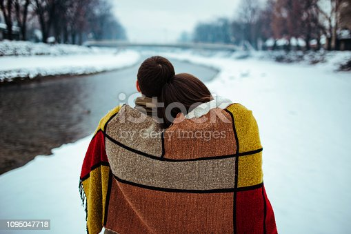 Portrait of pretty boy and cute girl rolled up in a blanket to keep themselves warm