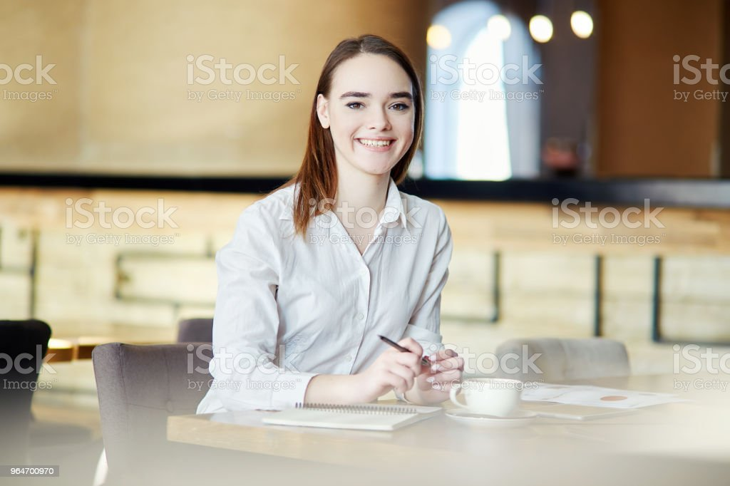 Portrait of pretty businesswoman looking at camera and smiling while sitting table in cafe with pen in her hands royalty-free stock photo