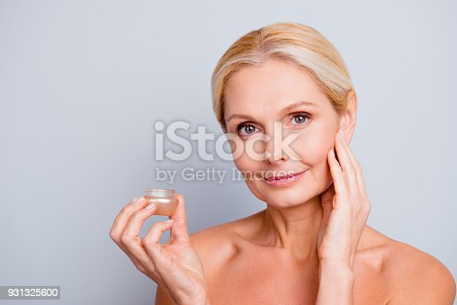 istock Portrait of pretty, charming, attractive, pure, nude woman having jar with face cream in hand, using, applying lotion, enjoying, touching her cheek, isolated on grey background 931325600
