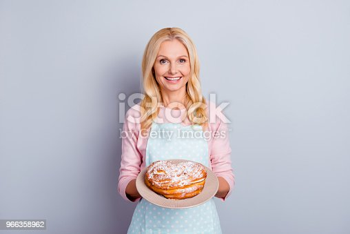 istock Portrait of pretty charming cheerful aged woman with wrinkle showing gesturing sweet homemade pie tasty bun isolated on grey background, specialty of the house 966358962