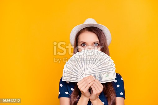 Portrait of pretty, charming, girl holding in hand a lot of money, close with fan half face, looking out with eyes, having white hat on head, isolated on yellow background