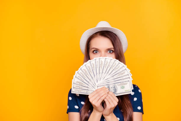 Portrait of pretty, charming, girl holding in hand a lot of money, close with fan half face, looking out with eyes, having white hat on head, isolated on yellow background stock photo