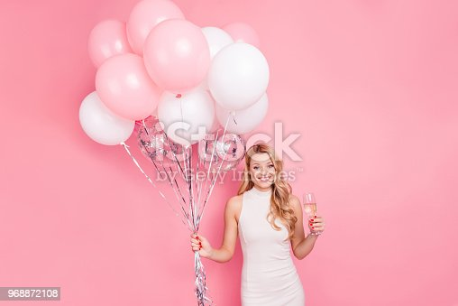istock Portrait of pretty charming girlfriend having air balloons and sparkling wine beverage in hands looking at camera isolated on pink background 968872108