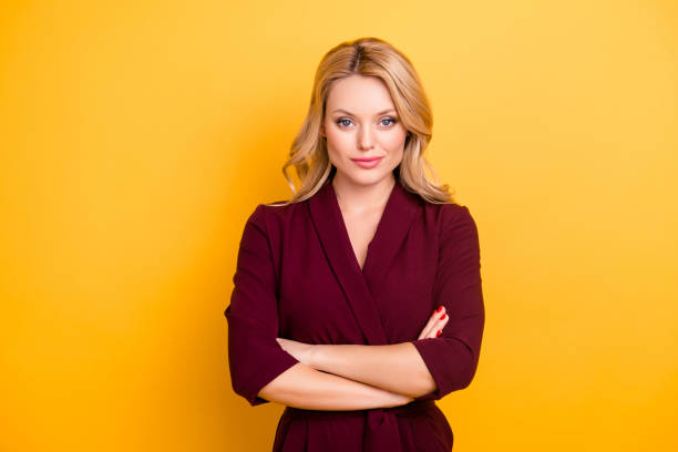 Portrait of pretty charming  woman in burgundy suit having her arms crossed looking at camera isolated on yellow background Portrait of pretty charming  woman in burgundy suit having her arms crossed looking at camera isolated on yellow background smirking stock pictures, royalty-free photos & images