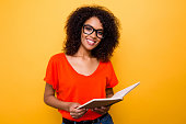 Portrait of pretty cheerful girl in eyewear holding open diary notepad in hands looking at camera isolated on yellow background