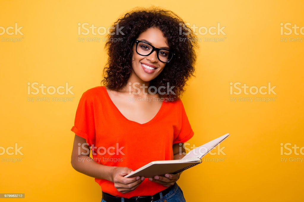 Portrait of pretty cheerful girl in eyewear holding open diary notepad in hands looking at camera isolated on yellow background stock photo