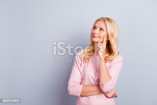 istock Portrait of pretty cute nice glad lovely beautiful excited rejoicing joyful cheerful with long wavy curly hairdo looking up to aside touching chin with hand isolated on gray background copysapce 932315522