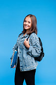 Happy teenage girl wearing oversized denim jacket, white t-shirt, black jeans and backpack standing against blue background. Pretty teenager holding books and notebooks.