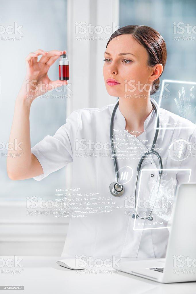 Portrait of pretty female laboratory assistant analyzing a blood stock photo