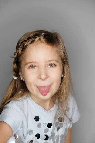 Portrait of pretty  funny little girl showing tongue. stock photo