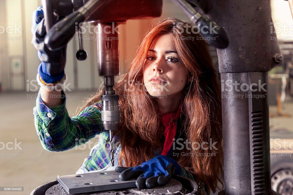 portrait of pretty girl at work on industrial drilling machine stock photo