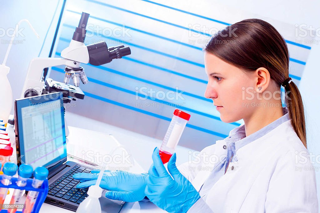 Portrait of pretty girl laboratory assistant analyzing a blood s stock photo