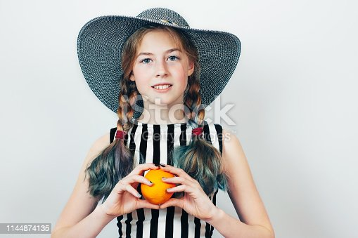 Elegant teen beautiful girl in hat and striped dress holding orange on grey background.