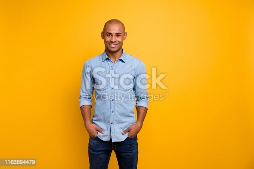 1163696387 istock photo Portrait of pretty guy feel glad hands palms pockets isolated over yellow background 1163694479
