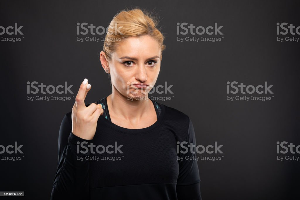 Portrait of pretty gym female trainer showing fingers crossed royalty-free stock photo