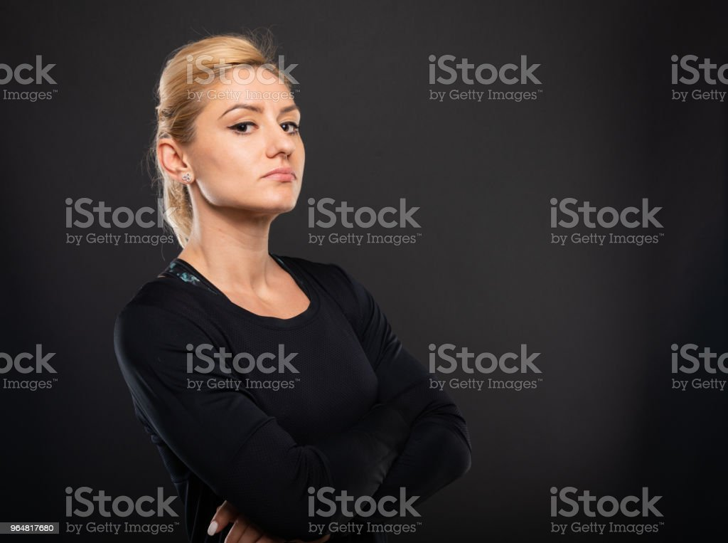 Portrait of pretty gym female trainer standing with arms crossed royalty-free stock photo