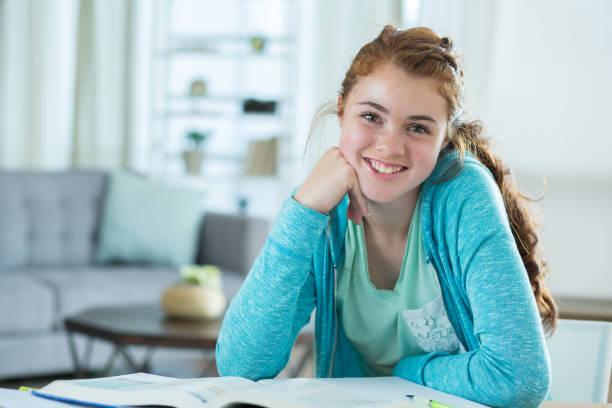 porträt von hübschen gymnasiastin arbeiten an hausaufgaben - haushaltsbuch führen stock-fotos und bilder