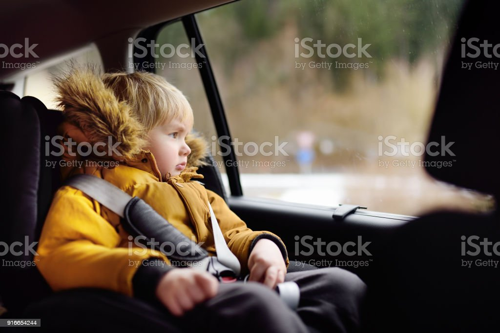 Portrait of pretty little boy sitting in car seat during roadtrip or travel stock photo
