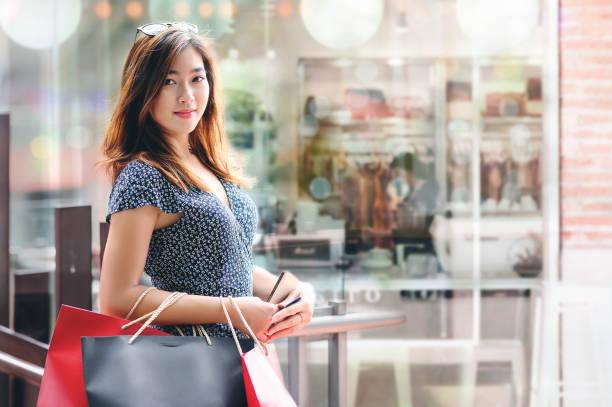 Retrato de mujer bonita en ropa casual con bolsas de compras de pie en el centro comercial. - foto de stock
