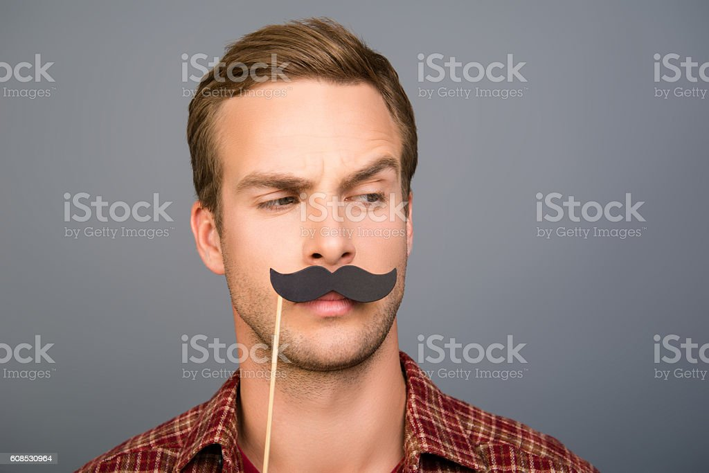 Portrait of pretty young man with paper mustache stock photo
