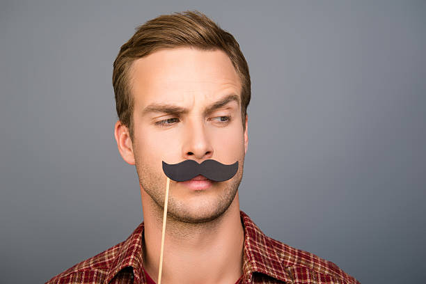 portrait of pretty young man with paper mustache - mustache stock pictures, royalty-free photos & images
