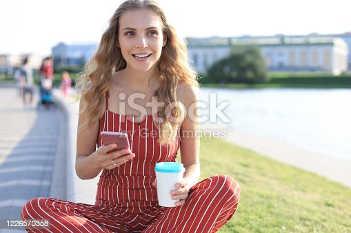 Portrait of pretty young woman sitting on riverbank with legs crossed during summer day, using smartphone.