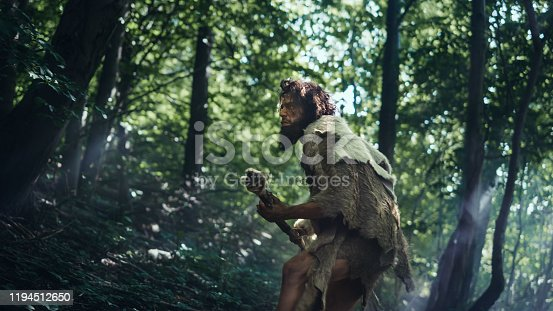 841481956 istock photo Portrait of Primeval Caveman Wearing Animal Skin and Fur Hunting with a Stone Tipped Spear in the Prehistoric Forest. Prehistoric Neanderthal Hunter Scavenging with Primitive Tools in the Jungle 1194512650