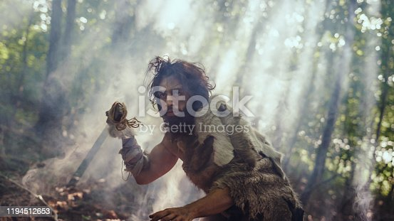 841481956 istock photo Portrait of Primeval Caveman Wearing Animal Skin and Fur Hunting with a Stone Tipped Spear in the Prehistoric Forest. Prehistoric Neanderthal Hunter Scavenging with Primitive Tools in the Jungle 1194512653