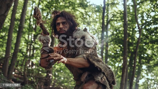 841481956 istock photo Portrait of Primeval Caveman Wearing Animal Skin and Fur Hunting with a Stone Tipped Spear in the Prehistoric Forest. Prehistoric Neanderthal Hunter Ready to Throw Spear in the Jungle 1194512681