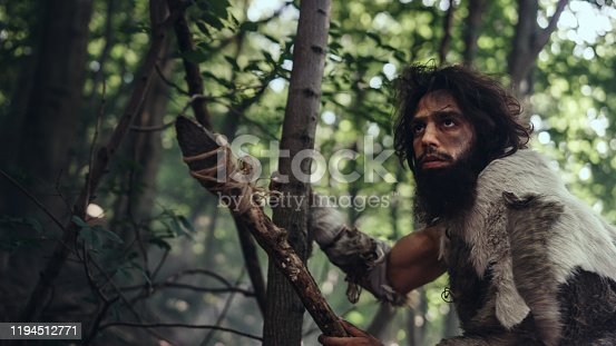 841481956 istock photo Portrait of Primeval Caveman Wearing Animal Skin and Fur Hunting with a Stone Tipped Spear in the Prehistoric Forest. Prehistoric Neanderthal Hunter Ready to Throw Spear in the Jungle 1194512771