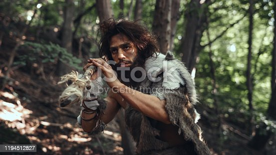 841481956 istock photo Portrait of Primeval Caveman Wearing Animal Skin and Fur Hunting with a Stone Tipped Spear in the Prehistoric Forest. Prehistoric Neanderthal Hunter Scavenging with Primitive Tools in the Jungle 1194512827