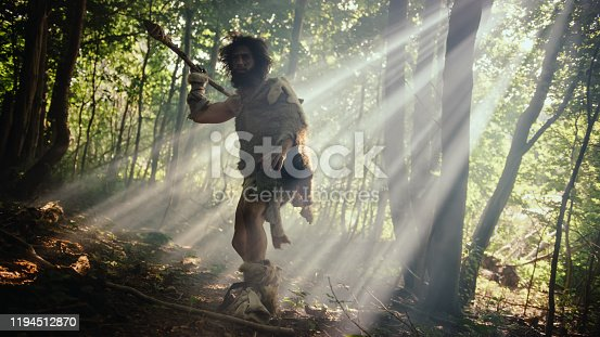 841481956 istock photo Portrait of Primeval Caveman Wearing Animal Skin and Fur Hunting with a Stone Tipped Spear in the Prehistoric Forest. Primitive Neanderthal Hunter Ready to Throw Spear in the Jungle 1194512870