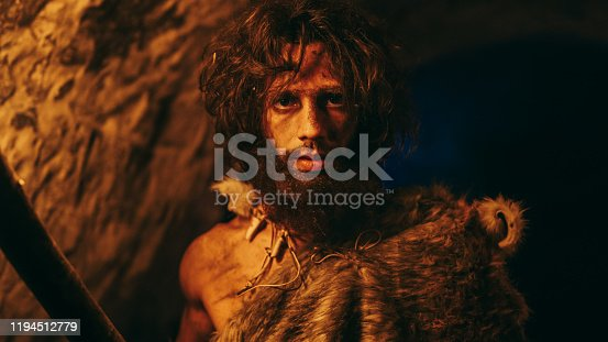 841481956 istock photo Portrait of Primeval Caveman Wearing Animal Skin Exploring Cave At Night, Holding Torch with Fire Looking into Camera at Night. 1194512779