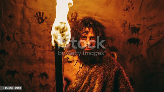 841481956 istock photo Portrait of Primeval Caveman Wearing Animal Skin Standing in His Cave At Night, Holding Torch with Fire. Primitive Neanderthal Hunter / Homo Sapiens At Night Alone. In the Background Cave Art Drawings 1194512889