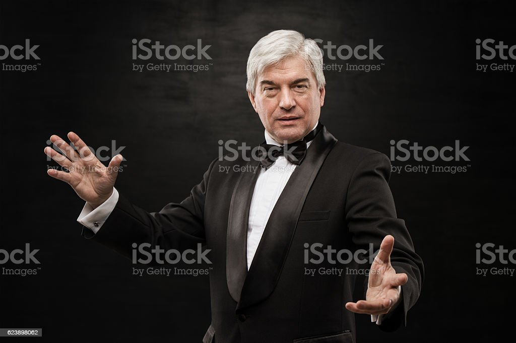 Portrait of professional hypnotist on black background stock photo
