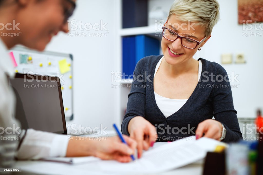 Portrait of professional middle aged women sits one across another and working together on projects in the office. stock photo