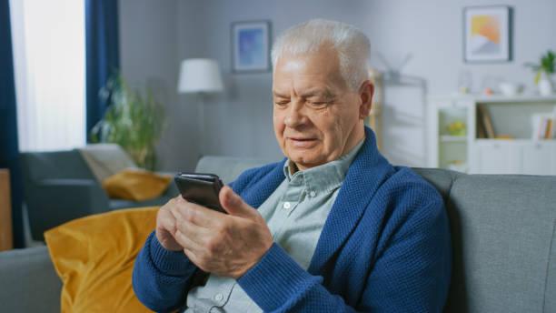 Porträt von Progressive Senior Mann sitzen in seinem Wohnzimmer verwendet leicht Smartphone, tut berührende Gesten und fühlt sich sehr komfortabel mit neuen Technologien. – Foto