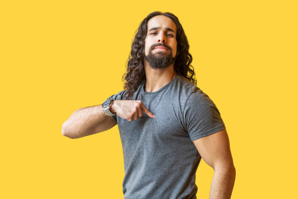 Portrait of proud bearded young man with long curly hair in grey tshirt standing, pointing himself and looking at camera with confident serious face. Portrait of proud bearded young man with long curly hair in grey tshirt standing, pointing himself and looking at camera with confident serious face. indoor studio shot isolated on yellow background. arrogant stock pictures, royalty-free photos & images